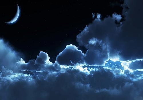 Dark blue moon above the clouds