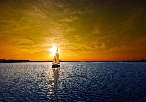 sun behind sailboat at dusk